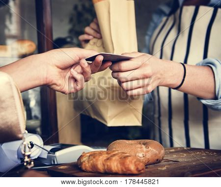 Buyer and seller at pastry shop paying by credit card