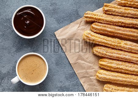 Churros Spain or Mexican breakfast meal street food baked sweet dough dessert with cup of coffee and chocolate dipping on rustic decorative parchment paper, blue background. Flat lay top view