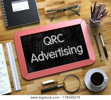 QRC Advertising on Small Chalkboard. QRC Advertising Handwritten on Red Chalkboard. Top View Composition with Small Chalkboard on Working Table with Office Supplies Around. 3d Rendering.