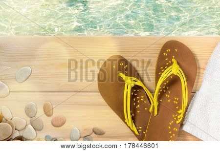 Summer beach vacation, flip flops, towel and sea pebbles on wood deck with clear transparent sea water on background.