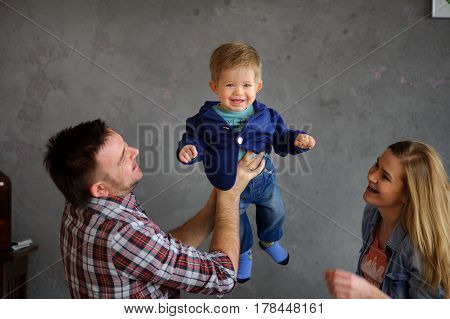 Young parents play with the little son. The kid joyfully laughs. The father and mother look at the child with love and tenderness.
