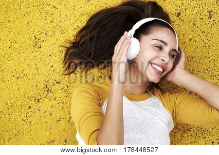 Young woman listening to music in headphones smiling