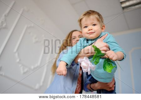 The young woman plays with the little son. In hands at the boy a flower. The child likes to play with mother. He smiles.