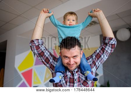 Little boy sits on the shoulders of his father. Young man playing with a child. Both the daddy and the kid smile.