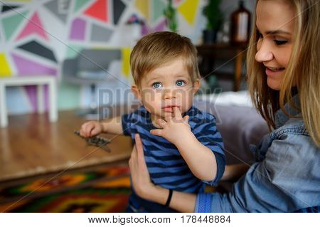 Mother plays with the little son. She with love and tenderness looks at the child. The amusing kid holds a finger in a mouth.
