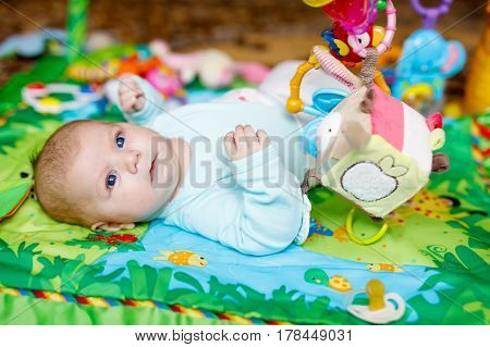 Cute adorable newborn baby playing on colorful toy gym and looking at the camera. Closeup of peaceful child, little baby girl learning to grab . Family, birth, new life. Attentive child.
