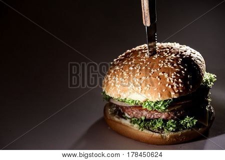Burger with vegetables and meat. Bun with sesame. Burger with knife in it.