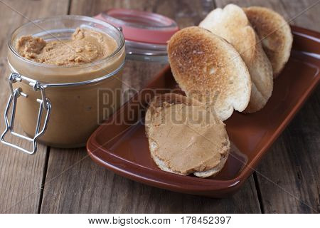 Toasts with peanut butter on a clay plate in a rustic style