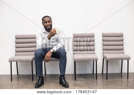 Time for job interview. Young handsome Afro-American man in office. Man sitting, holding cup of coffee, looking at camera and waiting for job interview. Empty chairs are near man. Nice light interior