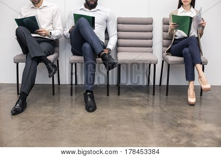 Time for job interview. Young men and woman in office. They sitting, holding CVs and waiting for job interview. Empty chair. Nice light interior