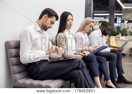 Time for job interview. Young men and women in office. They sitting, holding CVs and waiting for job interview. One man looking at watch. Nice light interior