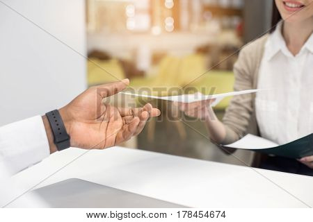 Time for job interview. Close up photo of young woman in office while job interview. She giving CV to employer. Nice light office interior