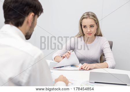 Young businessman and woman in office. They discussing graphs and business ideas. Nice light office interior