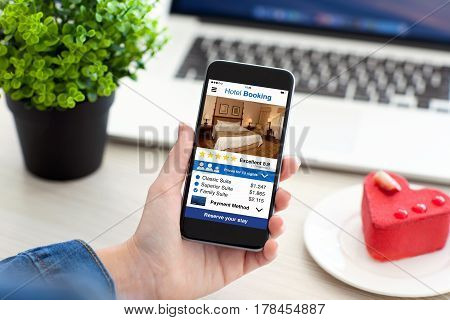 Women hand holding phone with app hotel booking screen table with notebook