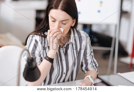 Terrible rhinitis. Inactive office worker wearing striped shirt keeping her eyes closed while turning head aside