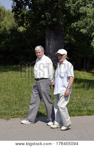Two old gentlemen walking in the park on a nice, sunny day
