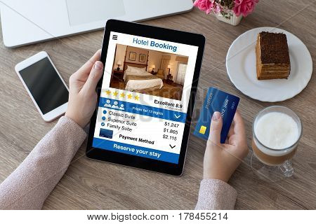 woman holding credit card and computer tablet with app hotel booking screen