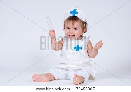 Cheerful girl child playing as a doctor with a syringe.