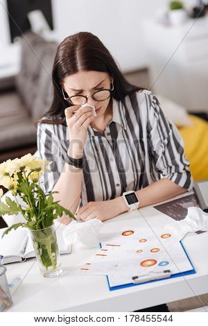 Work time. Serious office worker wearing glasses putting hands on the table while looking at documents
