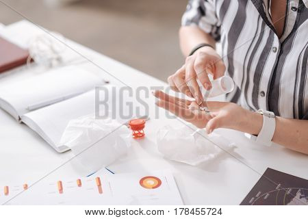 Just details. Photo of office worker wearing bracelet and watches holding pox from tablet while pouring out pills
