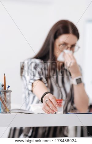 You may take. Sick female person holding box with medicine wiping her nose, sitting at her workplace