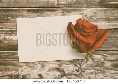 Vintage greeting card and rose on old wooden background