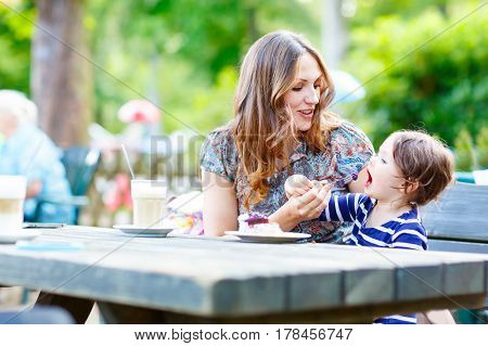 Young mother relaxing together with her little child, adorable toddler girl, in summer outdoors cafe drinking coffee and eating muffin or cupcke. Family in love. Kid an beautiful woman.