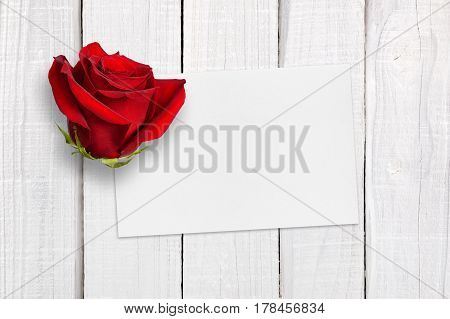 Greeting card and red rose on white wooden background