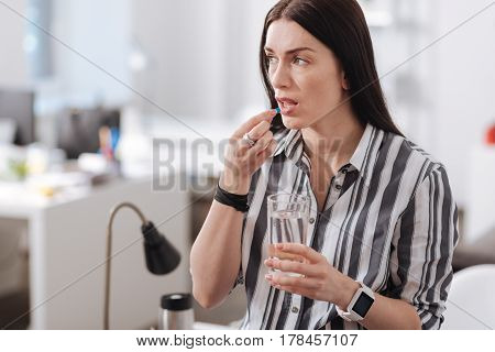 Think about future. Serious young woman holding glass in left hand putting tablet into mouth while looking sideways