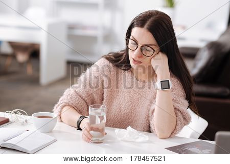 Think about something good. Thoughtful woman wearing pink cozy sweater looking on the table while taking glass