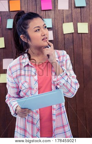 Thoughtful Asian woman with finger on chin holding tablet