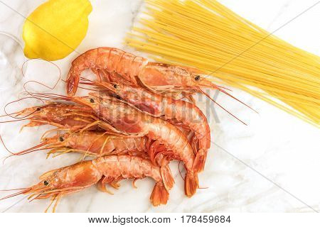 Raw shrimps with lemon and pasta, shot from above on a white marble table with a place for text