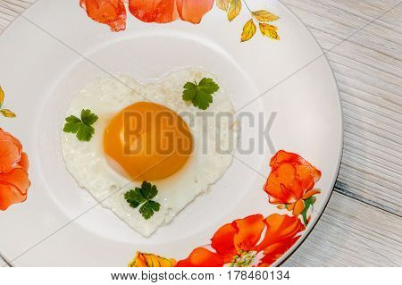 fried eggs in heart shape on the plate.