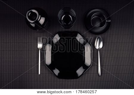 Black plate with cutlery on dark modern minimalistic mat background top view.