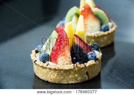 Mixed fruit tart. A custard base tart filling with various fruits on top.