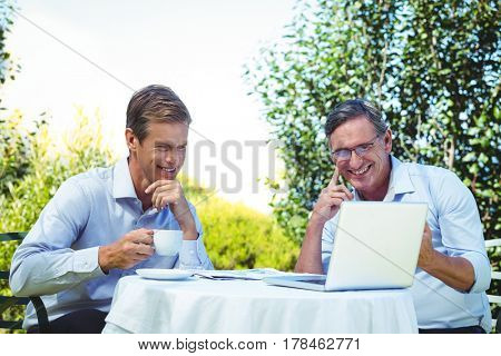 Casual businessman looking at laptop and having coffee on a terrace