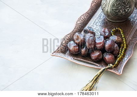 Dried Date Fruits Or Kurma Served On A Old Vintage Tray With Ornaments And Beads On A White Stone Ba