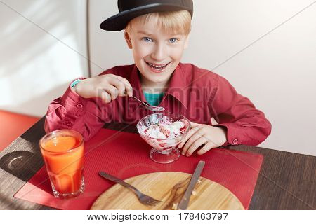A happy young boy with blue eyes and blond hair dressed in red shirt and stylish cap siting at cosy caffe eating delicious ice-cream and drinking tomato juice looking happily into a camera