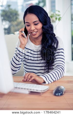 Smiling Asian woman on a phone call using computer in office