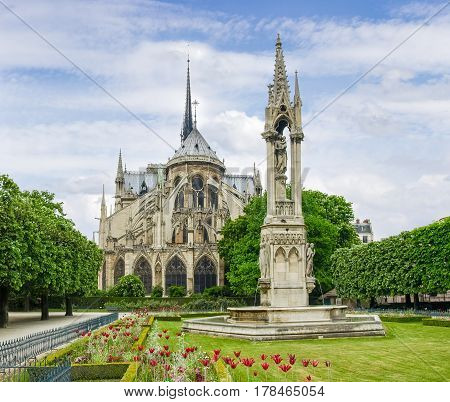 View of the eastern facade of the Cathedral Notre-Dame de Paris with the fontaine of Virgin on the foreground in springtime