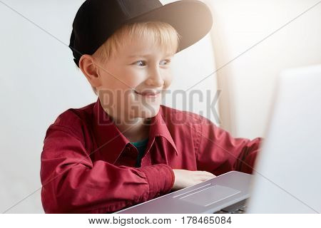 A happy little boy in trendy clothes relaxing during lunch at modern cafe sitting in front of open laptop having surprised expression while watching funny videos online using free internet connection