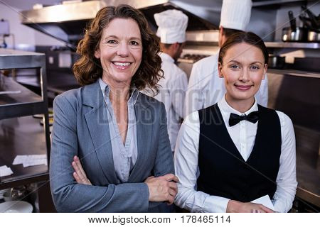 Portrait of female restaurant manager and waitress smiling in commercial kitchen