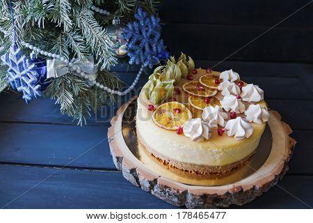 Christmas cake with cinnamon and orange decoration under Christmas tree
