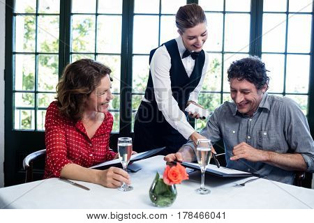 Waitress assisting a couple while selecting menu from menu card
