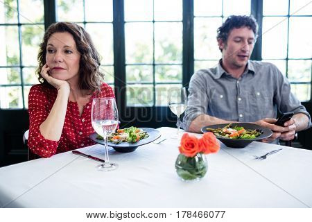 Woman feeling bored while man using his phone in restaurant