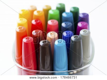 Colored markers in a cup on a white background.