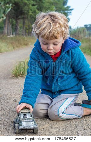 Small farm boy playing with toy car on dirt road