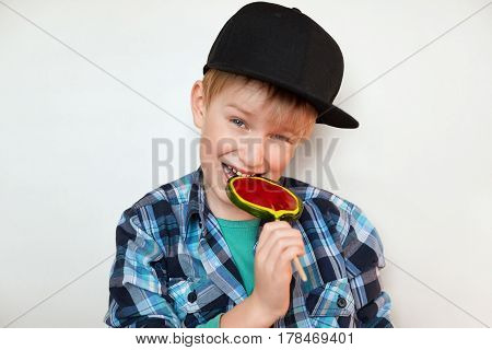 Headshot of beautiful little boy holding and biting lollipop looking at the camera with happy and joyful expression. Handsome boy in stylish clothes isolated over white background with sweet candy