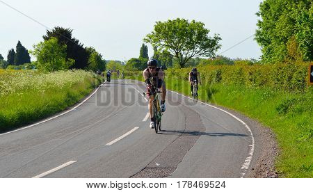 GRAFHAM, CAMBRIDGESHIRE, ENGLAND - MAY 22, 2016:  Triathletes on road cycling stage of triathlon fields and trees in background.