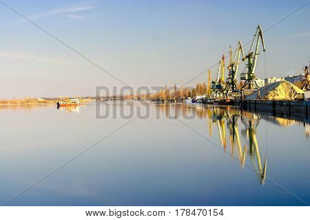 Row of cargo port cranes and floating barge reflected in calm river water